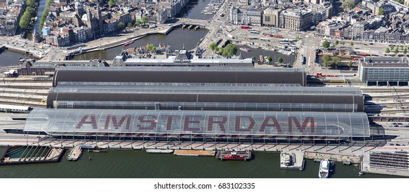 25 May 2017, Amsterdam. Aerial view of Central Station. The name of Amsterdam is written in huge letters on the roof at the side of river IJ