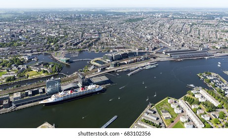 25 May 2017, Amsterdam. Aerial view of Amsterdam. In the front the passenger terminal with a huge cruiseship. On the clear horizon the UNESCO protected GRACHTENGORDEL.