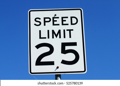 A 25 mile per hour sign against a blue sky