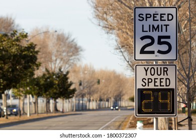 25 mph speed limit sign and radar speed indicator sign on a street.