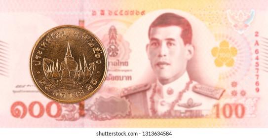 25 thai satang coin against 100 new thai baht banknote