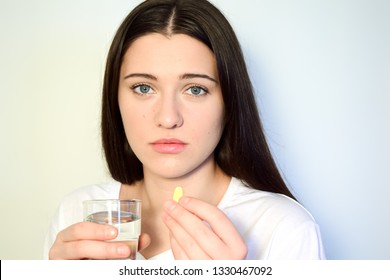 A 25 year old woman holds a glass of water and a pill. Close-up. Reception of medicines.