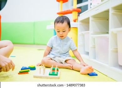 2.5 years old baby boy.Little child boy playing with lots of wooden toys block with mother.Kids play with educational toys for shape, color.Day care and Kindergarten school.child development concept.
