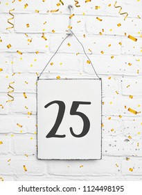 25 years old birthday party card text with golden confetti, number twenty-five, metal plate white brick background