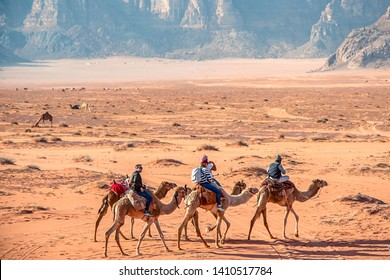 25/03/2019 Jordan, Wadi Rum, camels in incredible lunar landscape in Wadi Rum in the Jordanian desert with huge moon above. Wadi Rum also known as The Valley of the Moon