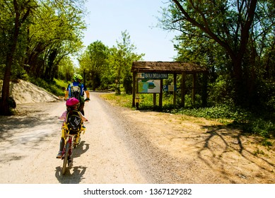 25.04.2018 Grado, Italy. Father and daughter going in bicycle to River Isonzo Mouth Reserve, destination writted in italian on board. The bike itinerary FVG2.