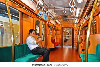 25.08.2017.man on green bench looks in his smartphone inside an empty carriage in a Tokyo subway train, Japan