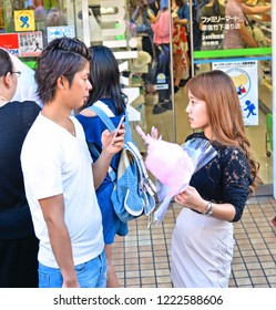 25.08.2017. a young couple is eating cotton candy on a street in Harajuku district in Tokyo Japan