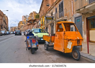 25.08.2018. vintage orange Ape Car and blue Vespa Piaggio on the street in Palermo, capital of Sicily in South Italy