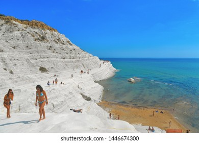 25.08.2018. white cliffs naturally made of smooth pug at Scala dei Turchi beach with group of young people with turquoise mediterranean sea and blue cloudy summer sky near Agrigento, Sicily, Italy