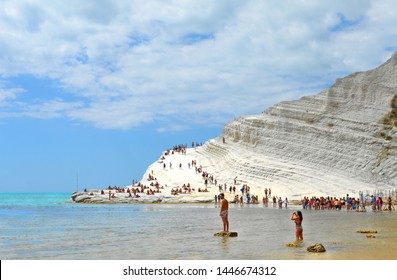 25.08.2018. white cliffs naturally made of smooth pug at Scala dei Turchi beach full of people with turquoise mediterranean sea and blue cloudy summer sky near Agrigento, Sicily, Italy