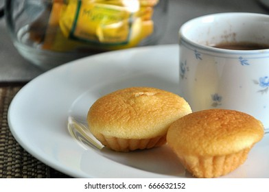 25-Jun-2017 Yangon, Myanmar : Cup of brown hot fresh Myanmar traditional authentic instant milk tea with pieces of homemade fresh baked soft cake or muffin or egg cake served for breakfast meal.