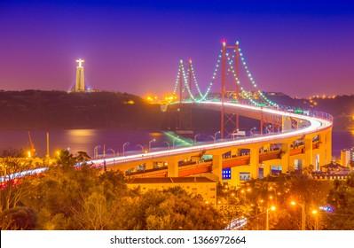 The 25th April Bridge (Ponte 25 de Abril) at night. Lisbon, Portugal.