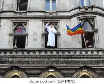 25th August 2018, Dublin, Ireland.  Papal visit to Ireland. A woman waves an LGBT pride flag next to a waxwork of pope Francis on a  windowsill on Westmoreland Street.