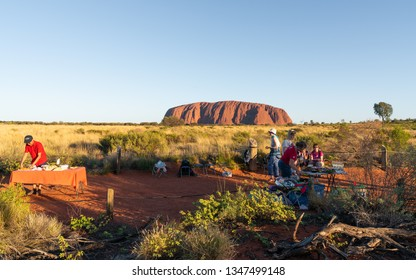 25th December 2018, Sydney NSW Australia : People setting dinner bbq buffet tables at Uluru sunset view point and Ayers rock in background in NT outback Australia