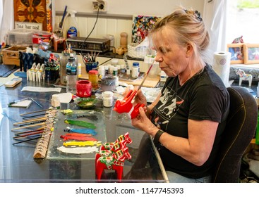 25th of July 2018, Sweden, Dalarna, Nusnäs; A woman paints the traditional wooden horse Dalahäst