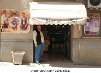 25th of May 2010 - Scene from Italian city with man standing outside a bar under an awning next to a poster from the movie Godfather, Corleone, Italy