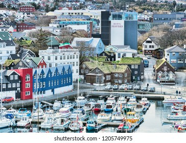 26 April 2018: Torshavn, Faroe Islands - The harbour, traditional grass roofed houses and the Hotel Hafnia in the town centre.