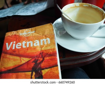 """26 July 2016 ,The book """"Lonely Planet"""", Vietnam edition ,was placed beside a cup of coffee"""