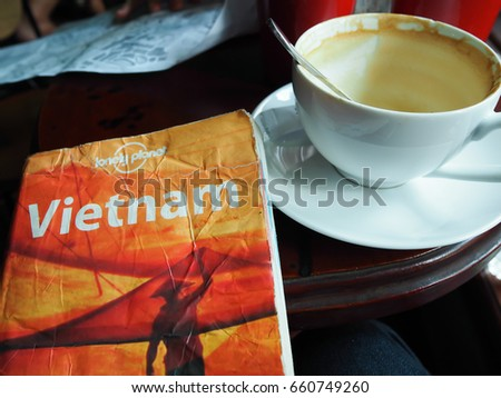 "26 July 2016 ,The book ""Lonely Planet"", Vietnam edition ,was placed beside a cup of coffee"
