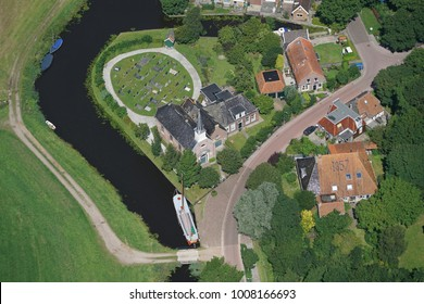 26 July 2017, Elahuizen, Holland. Aerial view of the Hervormde Kerk in a small village in the province of Friesland. It is a small medieval church with a cemetery.