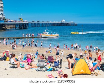 26 July 2018: Llandudno, Conwy, UK - Holidaymakers throng the beach and pier on one of the hottest days of the year, with bright sunshine and clear blue sky.