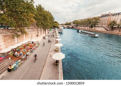 26 July 2019, Paris, France: People resting on a banks of Seine river