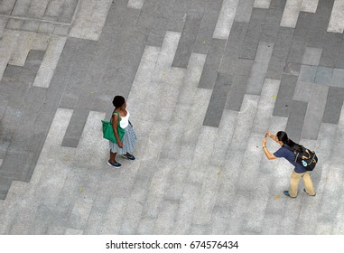 26 Jun 2017, Bangkok Thailand - Asian tourist girl or woman or female taking photo of her friendly smiling female african friend. Shot from top view or above.