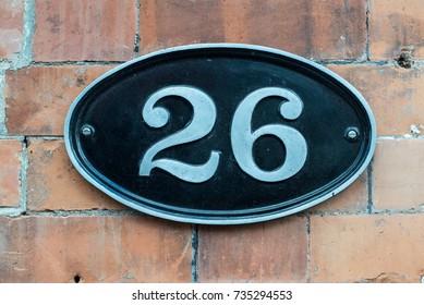 26 (twenty six) number metal plate on a purple wooden door