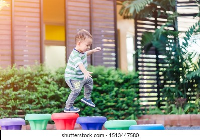 2.6 years old.Little toddler boy walking in colorful balance toy in playground at kindergarten school. Practice Gross Motor Skills concept.