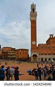 26.04.2019. Crowd of people and tourists relaxing in Piazza del Campo (Campo square) with Torre Mangia City Hall, facade of historical buildings in background in Siena, Tuscany, Italy