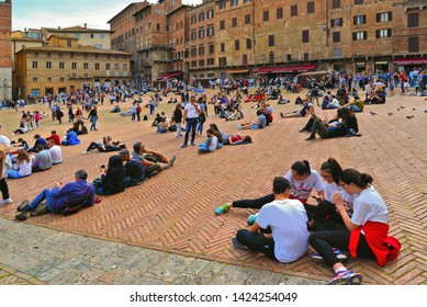 26.04.2019. Crowd of people and tourists relaxing in Piazza del Campo (Campo square) with facade of historical buildings in background in Siena, Tuscany, Italy