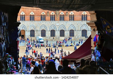 26.04.2019. Crowd of people and tourists walks in the passage through arch in Piazza del Campo (Campo square) with facade of historical buildings in background in Siena, Tuscany, Italy