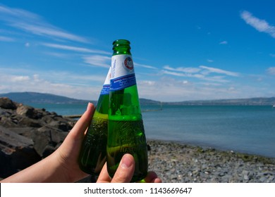 26.8.18 Holywood, Northern Ireland: couple holding bottles of peroni beer and do cheers against sea
