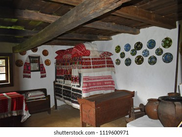 26-May-2018. The interior of a traditional Romanian house with old furniture and beautiful handmade decorations, towels and pillows at the Astra village  museum Sibiu, Transylvania, Romania, Europe.
