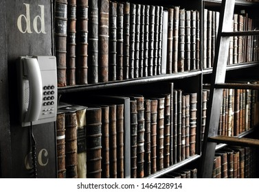 26th July 2019, Dublin, Ireland. Library phone and book categorization letters 'dd' next to a collection of books with a blurred focus books, in the Long Room of the Old Library at Trinity College.