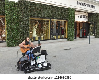 26th October 2018 Dublin. A busker playing a guitar outside the iconic Brown Thomas department store on Grafton Street. The store is decorated for Christmas with pine.