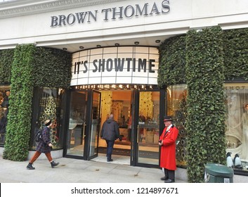 26th October 2018 Dublin. The iconic Brown Thomas department store on Grafton Street decorated for Christmas with pine. A doorman in red with bowler hat stands outside.
