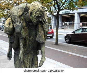 26th September 2018, Dublin, Ireland. Irish Famine memorial sculpture on Dublin Quays designed by Dublin sculptor Rowan Gillespie with IFSC, International Financial Services Centre across the road,
