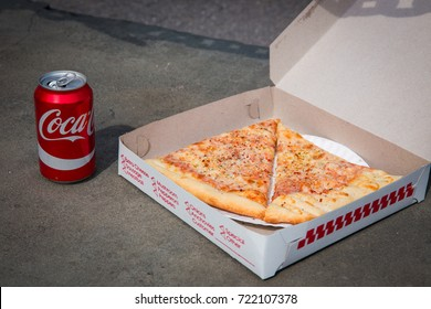 27 APRIL 2017 - NEW YORK - Legendary New York 0.99 cents slice pizza in box and can of coca-cola on grey background