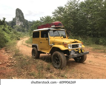 27 Mach 2017 , Jerantut, Malaysia, Yellow Toyota Land Cruiser FJ40 with boat at roof park at Sungai Pertang , Jerantut Pahang. One of larger rain forest conservation aria in National Park Malaysia