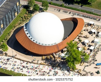 27 May 2017, Groningen, Holland. Aerial view of DOT Infoversum. A huge white modern projection dome. People are sunbathing at the city beach.
