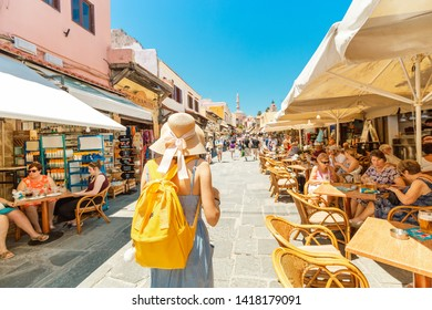 27 May 2019, Rhodes, Greece: Crowds of tourists walking and shopping at market street in Rhodos town, leading to famous Mosque