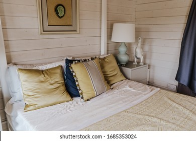 27.03.19 - Longacres Garden Center, England. Wooden house bedroom interior design. Comfortable bed with linen bedding and beige blanket, bedside table with lamp.