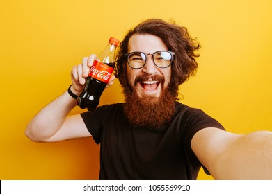 27/03/2018 Moldova Chisinau. Cheerful smiling bearded hipster man with Coca Cola Drink in hands. Man holding Coca Cola.