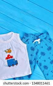 27.04.2018 - Kyiv, Ukraine. Beautiful set of baby boy clothing. Summer printed toddlers boy fashion clothes, blue wooden background.