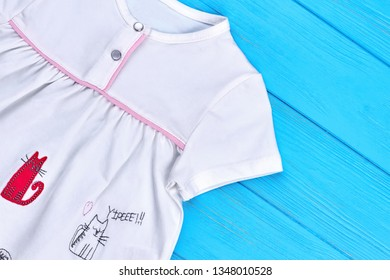 27.04.2018 - Kyiv, Ukraine. White organic cotton dress for baby-girl. Close up of baby textile gown with animal embroidery. Summer casual baby wear.