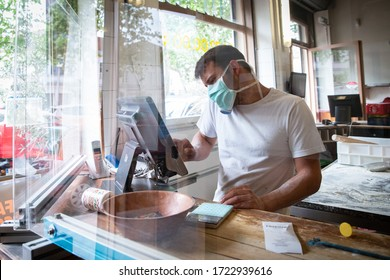 27/04/2020, Lyon, Rhoen Alpes Auvergne, France : Man is working in a pizza restaurant drive with his mask and covid 19 protection. Pandemic situation