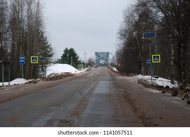 27th of December 2017 - Winter scene from Russian highway with view past zebra crossing to bridge over the river Luga, Ust Luga, Russia