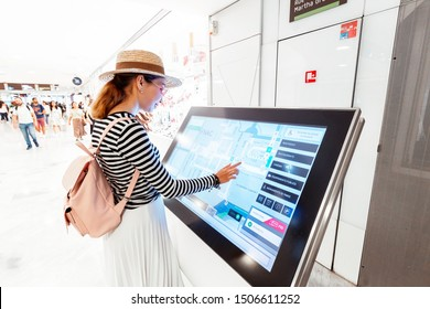 28 July 2019, Paris, France: Asian girl uses touchscreen terminal to find the right boutique in a big shopping Mall